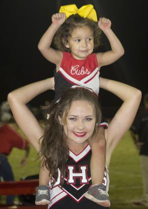 Olney High School Cheerleader Emma Barrington hold up Carliegh Symank while the cheerleading team raised funds for the Cooks Children Hospital Solid Tumor Research Fund.  Jimmy Potts/Enterprise