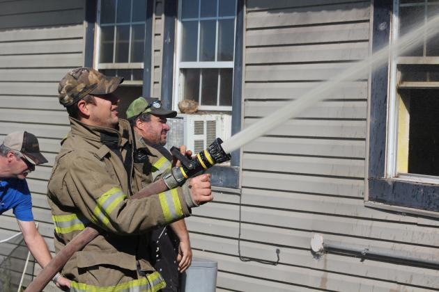 Olney Firefighter Jason Pack mans a hose during a house fire near the Young County/Archer County border.