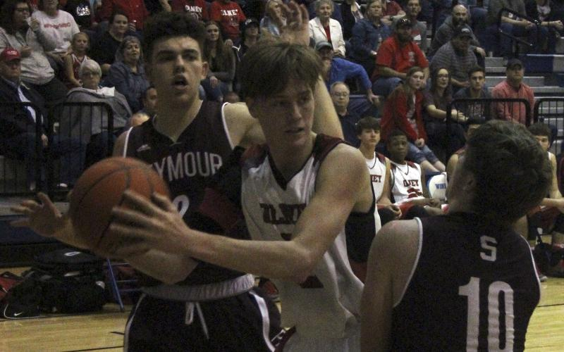 Olney High School senior guard Brent McCorkle fights of Seymour's aggressive defenders.