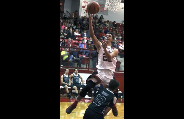 Olney High School senior forward Travis Hudson puts in a layup during the first half of a game against Santos.
