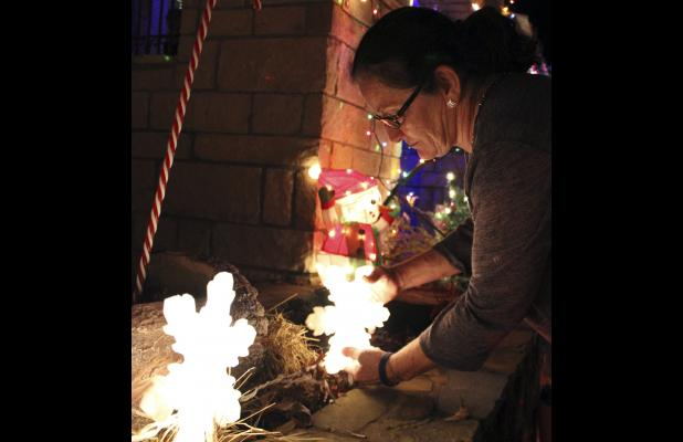 Edie Acuna makes a few adjustments to her decorations during a photo shoot Sunday night.