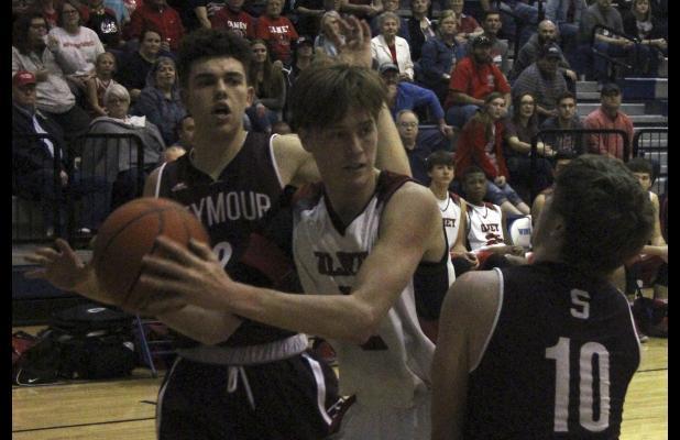 Olney High School senior guard Brent McCorkle fights of Seymour's aggressive defenders.